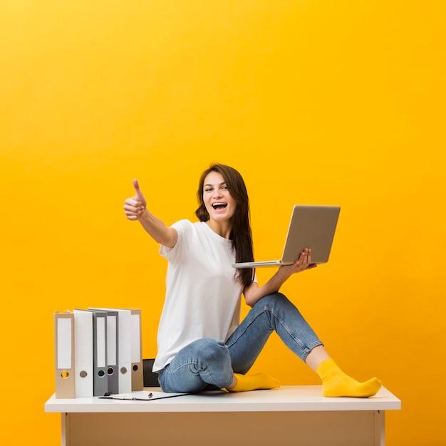 Vista lateral de la mujer sonriente sentada en el escritorio y dando pulgares mientras sostiene el portátil Foto gratis