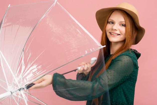 Vista lateral mujer sosteniendo paraguas Foto gratis