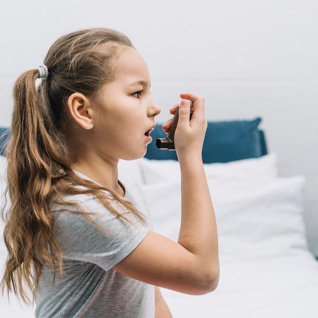 Vista lateral de una niña con inhalador de asma Foto gratis