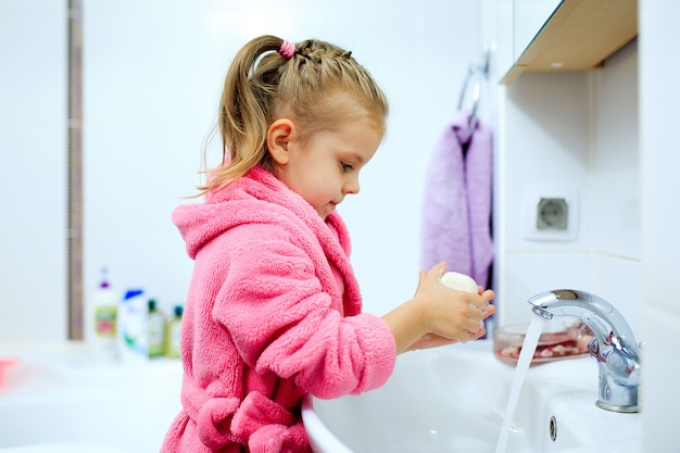 Vista lateral de la niña linda con cola de caballo en bata de baño rosa que se lava las manos. Foto Premium