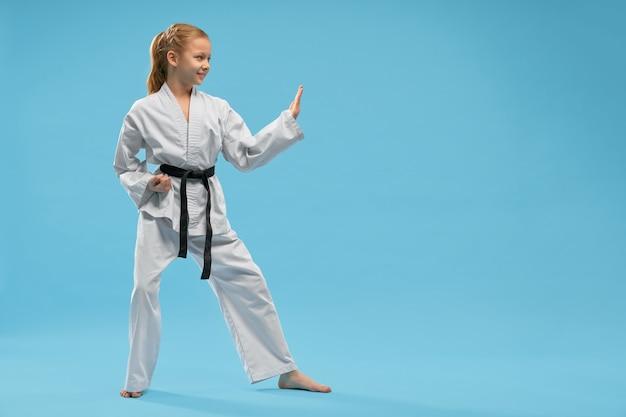 Vista lateral de la niña sonriente en kimono blanco karate de entrenamiento Foto gratis
