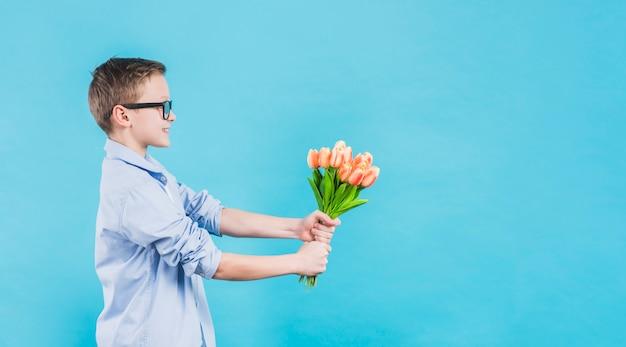 Vista lateral de un niño con lentes que dan tulipanes frescos sobre fondo azul Foto gratis