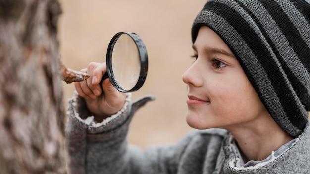 Vista lateral niño mirando a través de una lupa Foto gratis