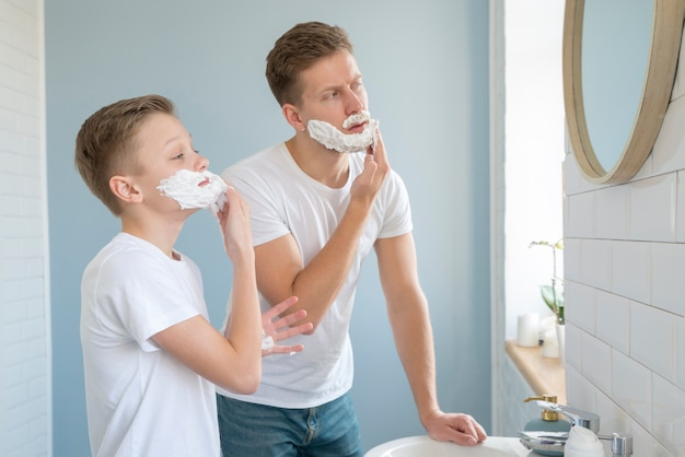 Vista lateral de niños usando espuma de afeitar Foto gratis