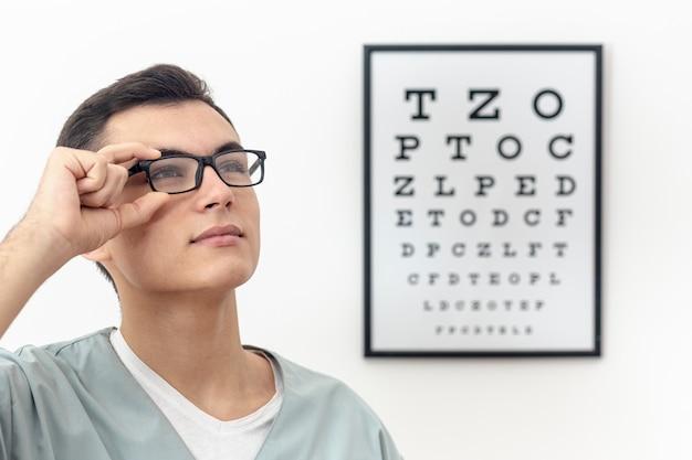 Vista lateral del oftalmólogo probándose un par de anteojos Foto Premium