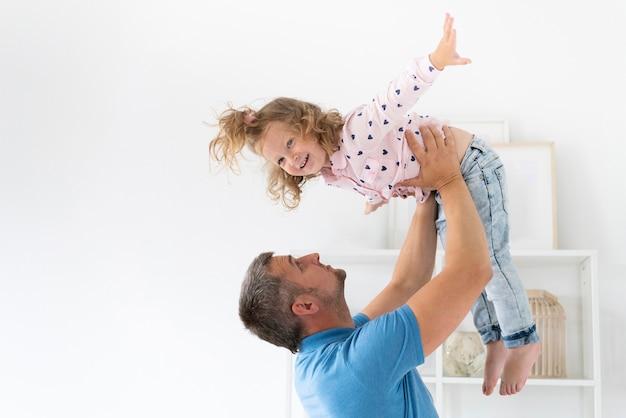 Vista lateral padre sosteniendo hija Foto gratis