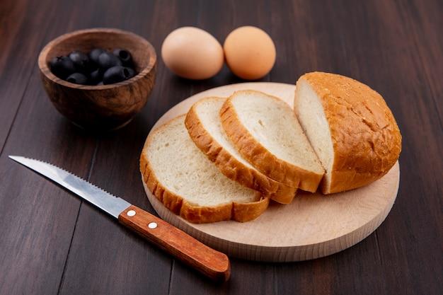 Vista lateral del pan de molde en la tabla de cortar y un cuchillo con huevos y tazón de aceituna negra sobre madera Foto gratis