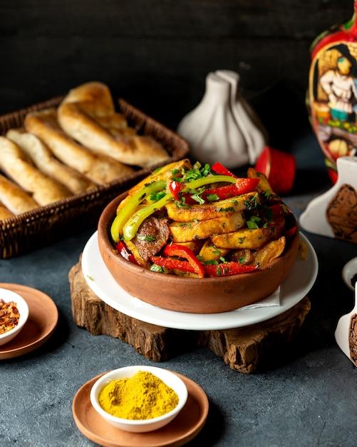 Vista lateral de papas al horno con carne de cordero y verduras en un recipiente de arcilla sobre la mesa negra Foto gratis