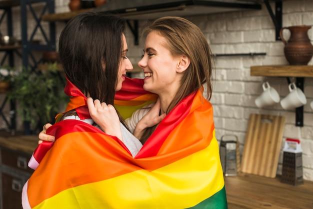Vista lateral de una pareja joven lesbiana romántica envuelta en una bandera lbgt Foto gratis