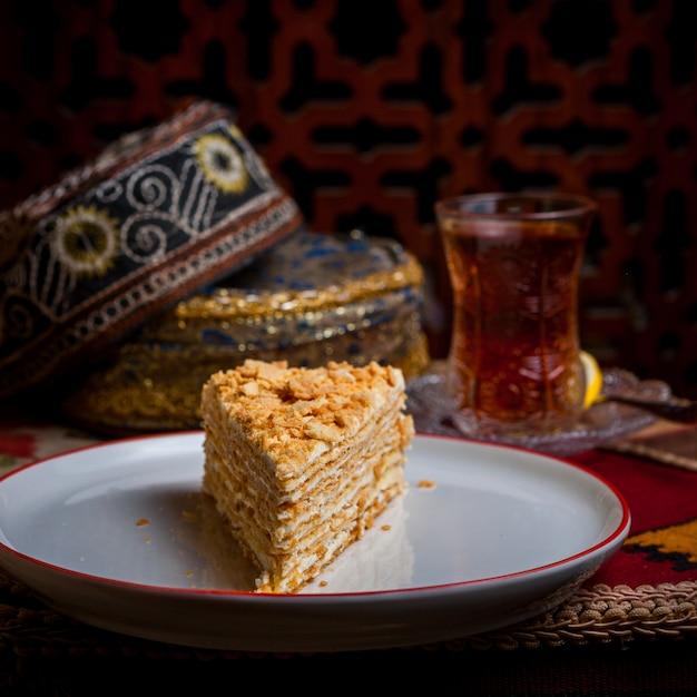 Vista lateral del pedazo de pastel con vaso de té y sombrero nacional y limón en plato blanco Foto gratis