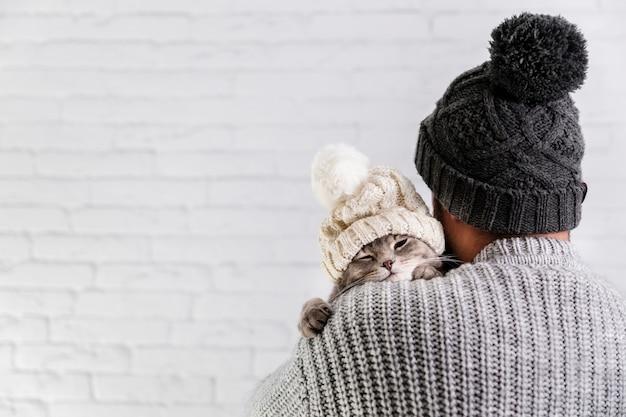 Vista lateral pequeño gatito con gorro de piel Foto gratis