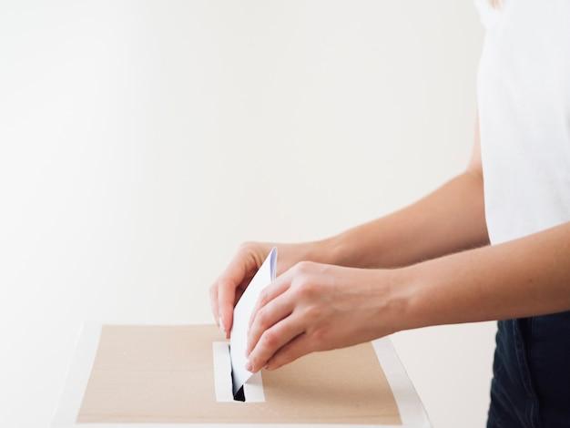 Vista lateral persona poniendo papeleta en la caja de elecciones Foto gratis