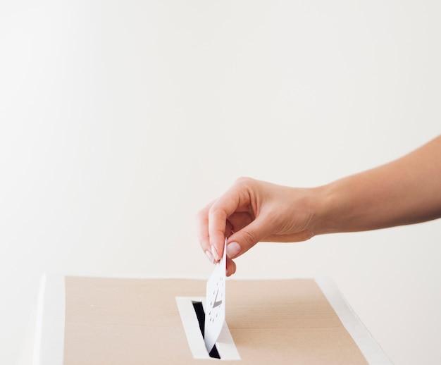 Vista lateral persona poniendo papeleta en la caja Foto gratis