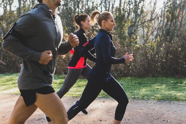 Vista lateral de personas corriendo en el parque Foto gratis