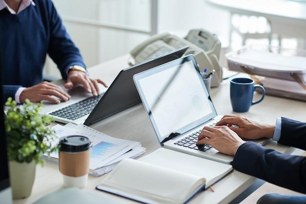 Vista lateral de personas de negocios recortadas irreconocibles que trabajan en un escritorio común Foto gratis