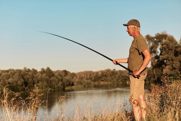 Vista lateral del pescador de pie en la orilla del lago o río y mirando su caña de pescar en las manos, pescando al atardecer, en la hermosa naturaleza, vistiendo pantalones y camiseta verde. Foto gratis