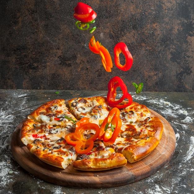 Vista lateral de pizza con rodajas de pimiento y rebanadas de pizza y harina en utensilios de cocina Foto gratis