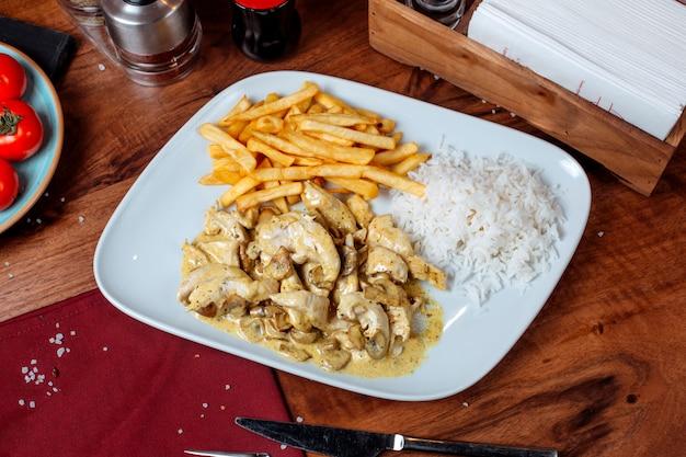 Vista lateral del pollo guisado en una salsa cremosa con champiñones con papas fritas en un plato blanco Foto gratis
