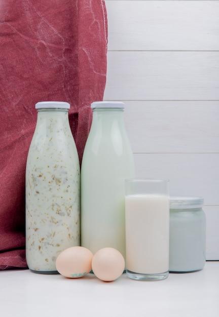 Vista lateral de productos lácteos como leche de sopa de yogurt azerbaiyano y leche agria coagulada con huevos sobre superficie blanca y superficie de madera Foto gratis