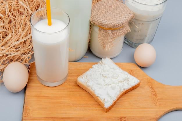 Vista lateral de los productos lácteos como queso cottage untado en rebanada de pan vaso de leche en la tabla de cortar crema de leche yogurt sopa y huevos con paja en la superficie azul Foto gratis