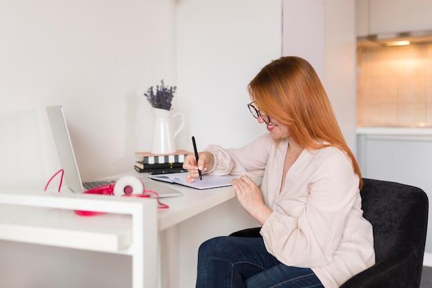 Vista lateral de la profesora durante la clase en línea en el escritorio Foto gratis