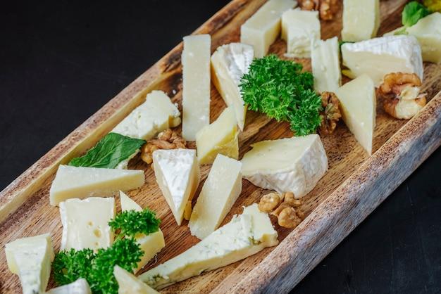 Vista lateral en rodajas de queso roquefort con hierbas y nueces en un plato de madera Foto gratis