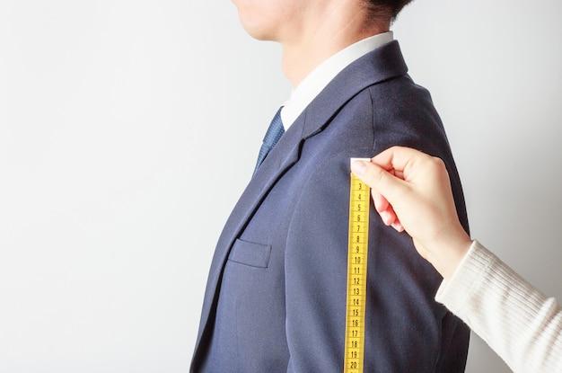 Vista lateral del sastre midiendo el traje de hombre Foto Premium
