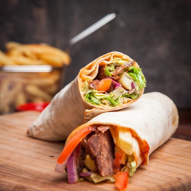 Vista lateral shawarma con papas fritas en utensilios de cocina Foto gratis