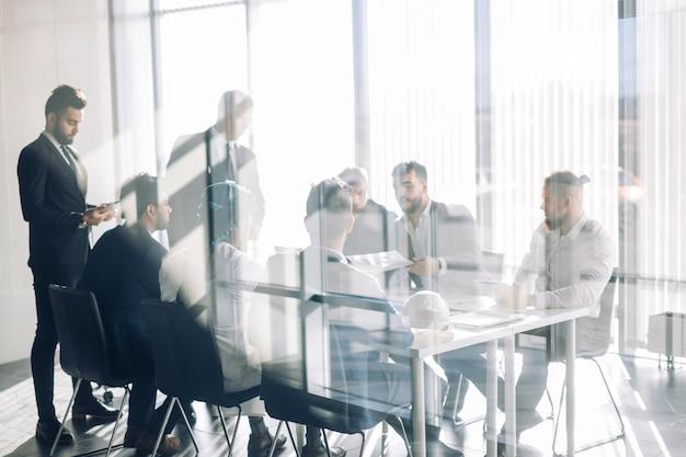 Vista lateral de siluetas borrosas de empresarios hablando en la sala de conferencias Foto Premium