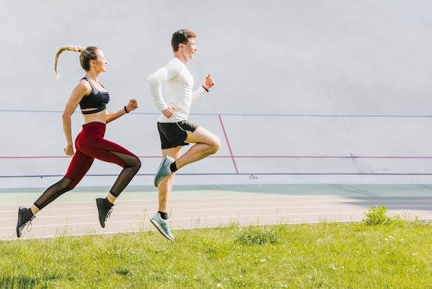 Vista lateral de socios corriendo Foto gratis