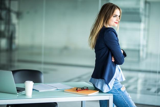 Vista lateral sonriente joven empresaria de pie en su lugar de trabajo Foto gratis
