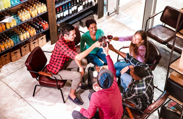 Vista lateral superior de amigos ricos degustando vino tinto y divirtiéndose en la bodega del bar de moda Foto Premium