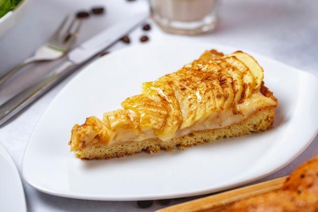 Vista lateral tarta de manzana con crema y canela en un plato Foto gratis