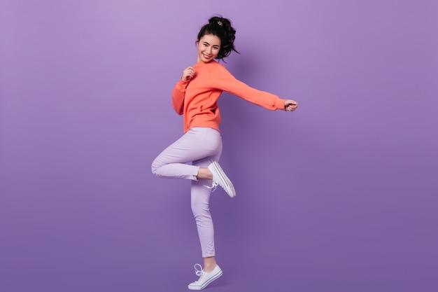 Vista de longitud completa de la alegre niña china de pie sobre una pierna. foto de estudio de modelo de mujer asiática sin preocupaciones bailando sobre fondo púrpura. Foto gratis