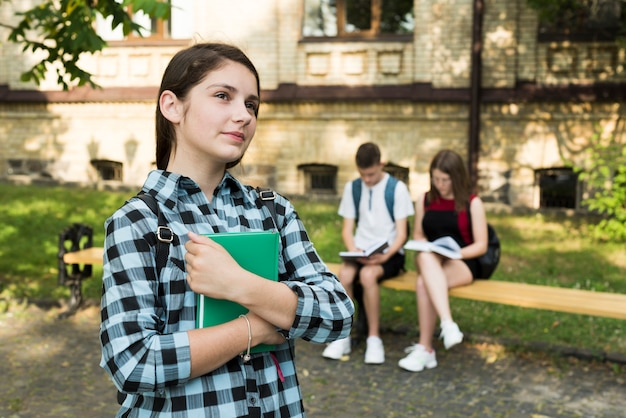 Vista media de tiro lateral de una chica de ensueño que sostiene un cuaderno Foto gratis