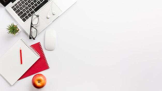 Vista panorámica del escritorio de oficina blanco con laptop, apple y papelería Foto gratis