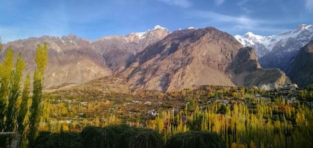 La vista panorámica del valle de hunza en otoño con nieve capsuló la montaña de ultar sar en el rango de karakoram. Foto Premium