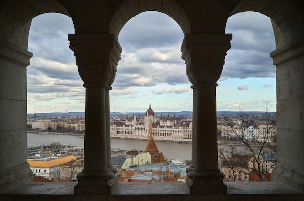 Vista del parlamento de budapest desde detrás de algunas columnas al otro lado del río. Foto Premium