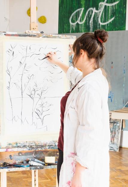 Vista posterior del artista femenina dibujando en lienzo con palo de carbón Foto gratis