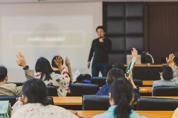 Vista posterior de la audiencia que muestra la mano para responder la pregunta del orador en el escenario de la sala de conferencias o reunión del seminario Foto Premium