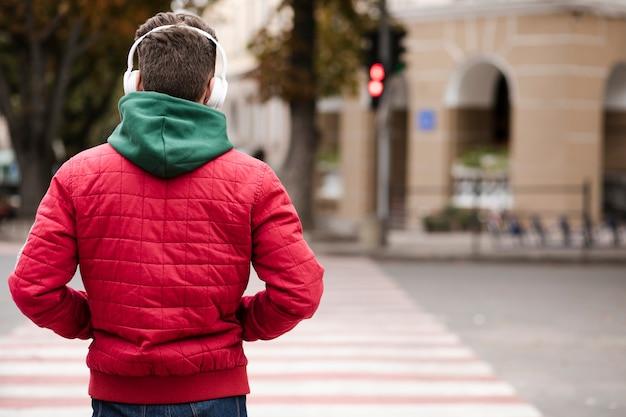 Vista posterior chico con auriculares al aire libre Foto gratis