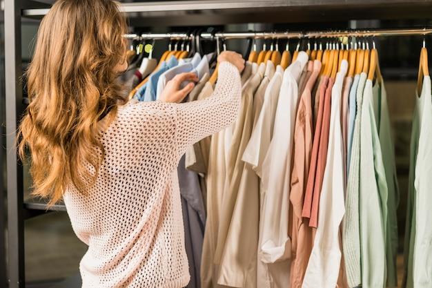 Vista posterior de un cliente femenino seleccionando prendas en la tienda. Foto gratis