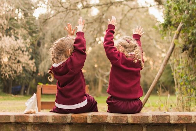 Vista posterior de dos niñas sentadas en el banco levantando sus manos Foto gratis
