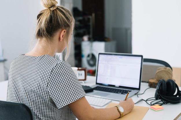 Vista posterior de una empresaria que escribe notas sobre el papel marrón con el ordenador portátil en el escritorio Foto gratis
