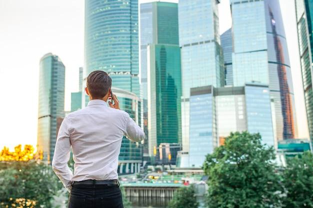 Vista posterior del empresario mirando el espacio de la copia mientras está de pie contra el rascacielos de cristal Foto Premium