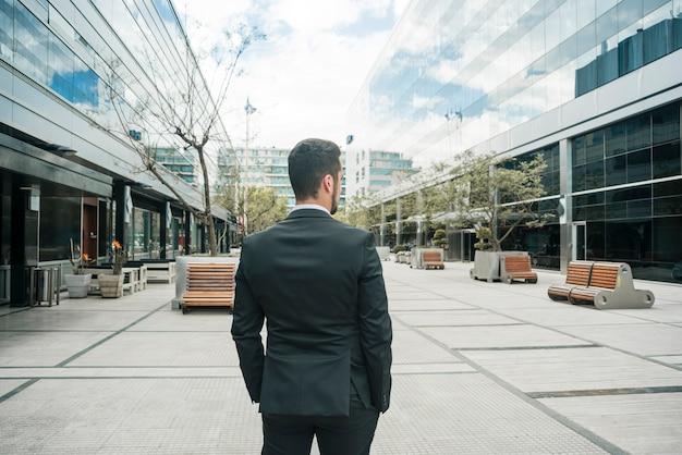Vista posterior de un empresario de pie en el campus de negocios Foto gratis