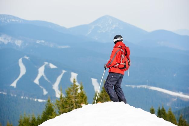 Vista posterior del esquiador masculino disfrutando en la cima de la pendiente en la estación de esquí Foto Premium