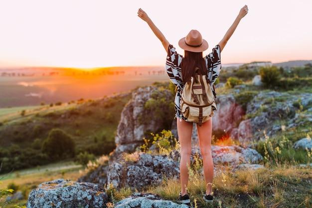 Vista posterior de un excursionista femenino con el brazo levantado Foto gratis