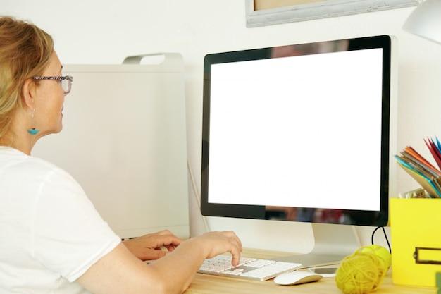 Vista posterior de una hermosa mujer madura con una camiseta blanca usando una pc con una pantalla de espacio de copia en blanco para su texto promocional o contenido publicitario, pagando facturas domésticas en línea, revisando el correo electrónico Foto gratis