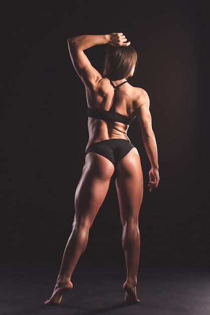 Vista posterior de hermosa mujer musculosa fuerte. Foto Premium